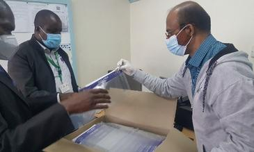 A team of LSTM and Technical Quality subcommittee at National Ministry of Health inspect sample face shields from a supplier for quality assurance.