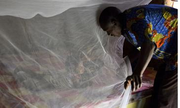 Father putting his daughter under a bednet in Burkina Faso - ©Jed Stone