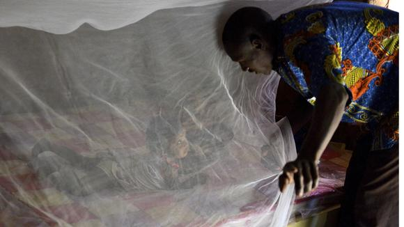 Father putting his daughter under a bednet in Burkina Faso