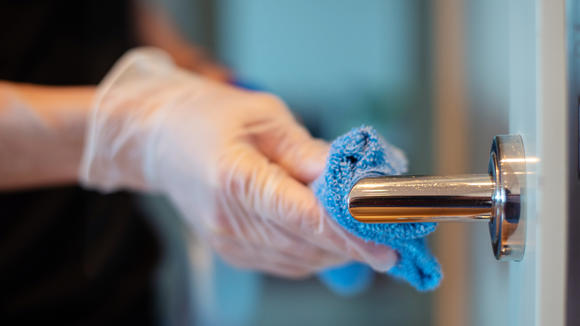 Door handle being cleaned with disinfectant